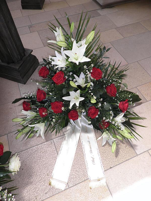 Gesteck aus roten Rosen und weißen Lilien