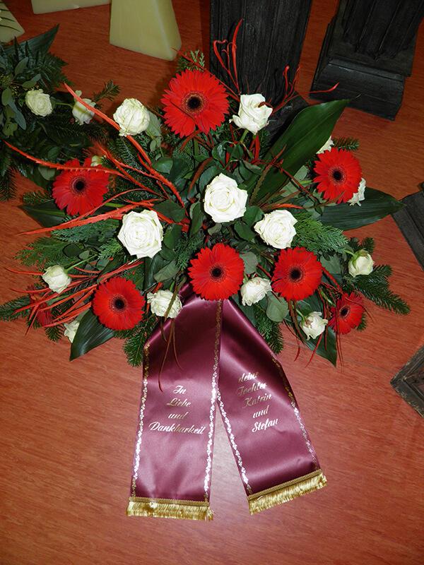 Gesteck aus roten Gerbera und weißen Rosen
