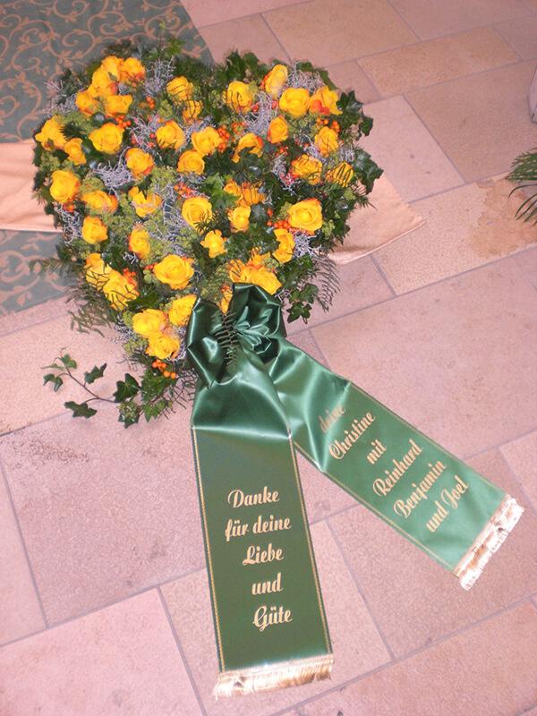 Herzgesteck aus gelben Rosen mit grüner Schleife