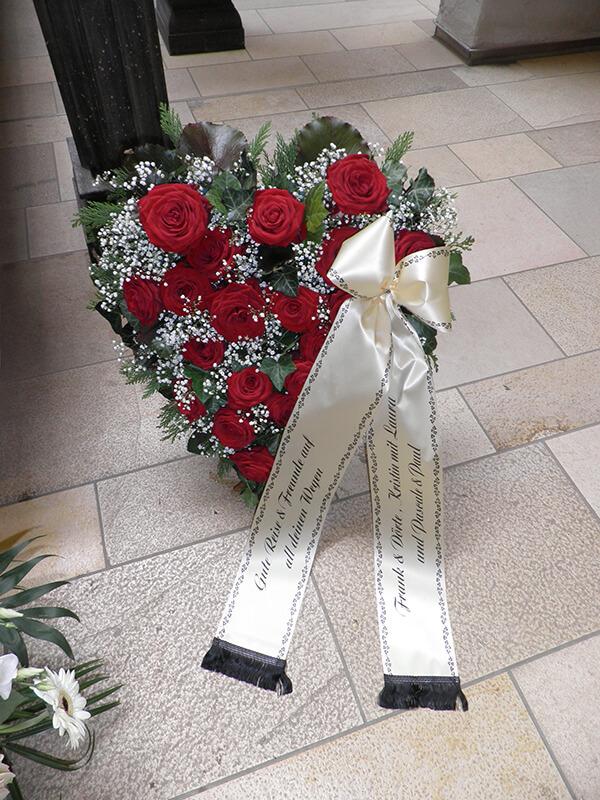 Herzgesteck aus roten Rosen und Schleierkraut