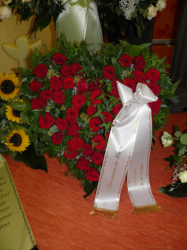 Herzgesteck mit roten Rosen und weißer Schleife