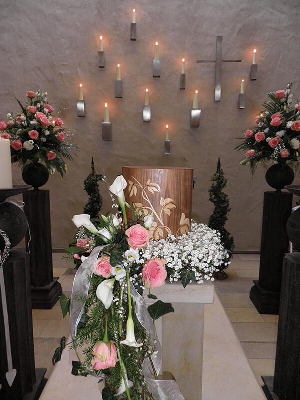 Holzurne mit rosa Rosen und Callas geschmückt