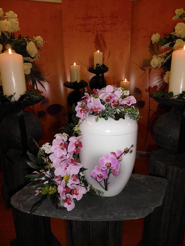 weiße Urne mit weiß-rosa Orchideen geschmückt