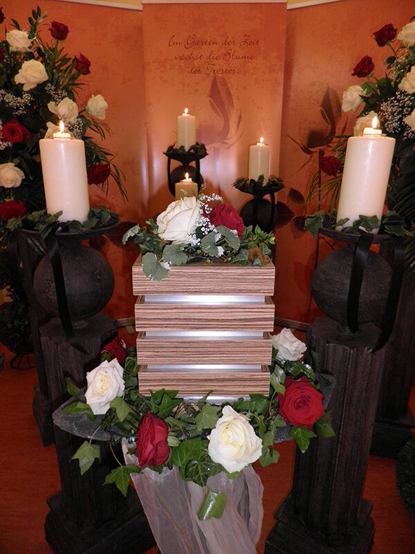 Quader-förmige Urne mit roten und weißen Rosen geschmückt