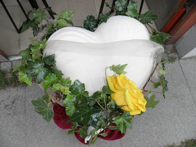 weiße Urne in Herzform mit Efeu umrankt und einer gelben Rose