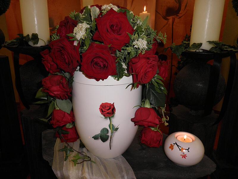 weiße Urne mit roten Rosen geschmückt