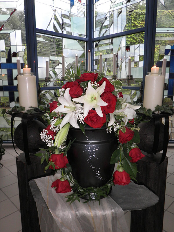 schwarze Urne mit roten Rosen und weißen Lilien geschmückt