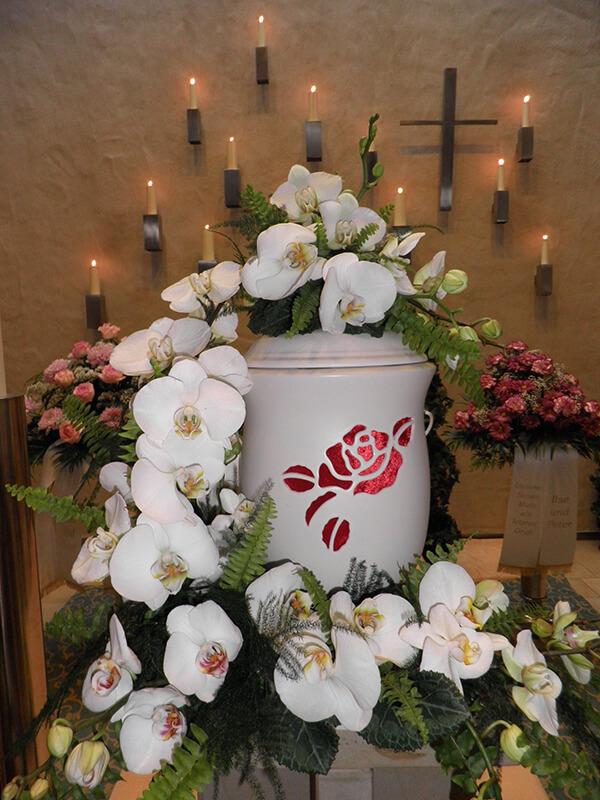 weiße Urne mit rotem Rosenmotiv, geschmückt mit weißen Orchideen
