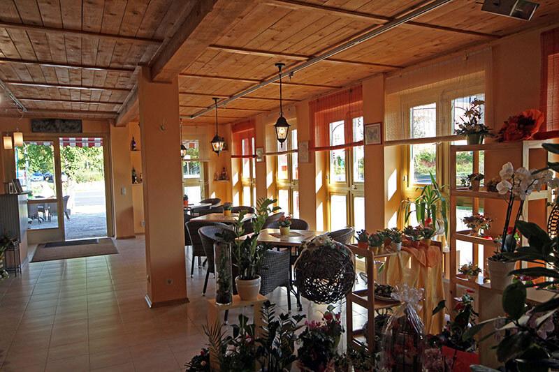 Raum mit Café-Tischen und Blumen-Ausstellung
