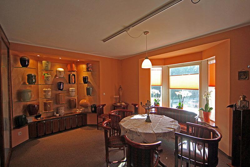 Raum mit Urnen-Ausstellung und Sitzgruppe mit Tisch und Stühlen