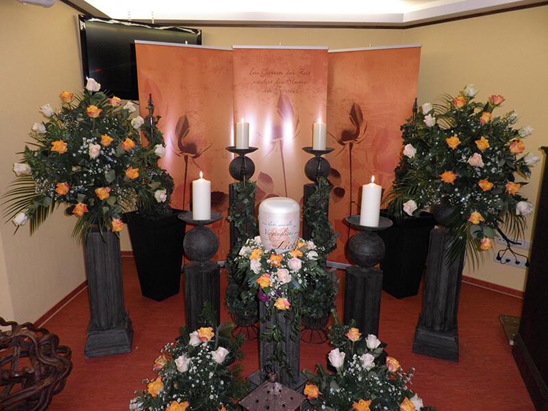 Aufbahrung mit Urne und Rosen-Blumenschmuck in weiß und gelb-orange