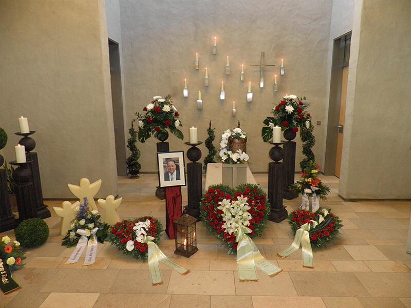 Aufbahrung mit Urne und Blumenschmuck in rot und weiß